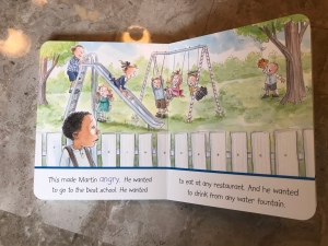 "A page in the board book of The Story of Martin Luther King Jr that reads, ""This made Martin angry. He wanted to go to the best school. He wanted to eat at any restaurant. And he wanted to drink from any water fountain."" The illustration depicts a young King looking over a fence at white children playing on a playground."