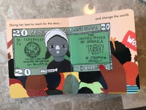 "A page of the board book Harriet that reads, ""Doing her best to reach for the stars... and change the world."" The image shows a $20 bill with Harriet Tubman being held up in front of protesters."