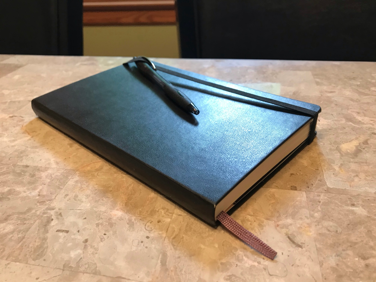 A black Moleskin journal with a black pen tucked into the band, sitting on a marble tabletop.